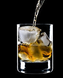 Glass of whiskey and ice under the pouring whiskey Royalty Free Stock Images