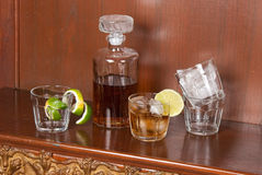 Glass with whiskey and ice on a wood table Stock Images