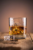 Glass of whiskey with ice. On wooden background Stock Images