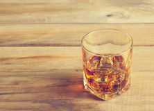 Glass of whiskey with ice on wooden background, Vintage color to Stock Photography