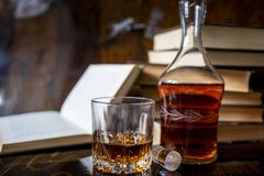 Glass of whiskey and ice on wooden table stock photography