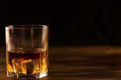 Glass of whiskey with ice on a wooden table. Royalty Free Stock Photos