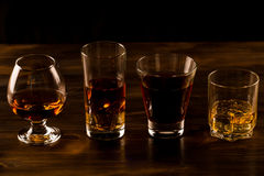 Glass of whiskey with ice on a wooden table. Royalty Free Stock Image