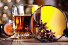 Glass of whiskey, magnifying glass, anise and cinnamone. Whiskey, magnifying glass, anise and cinnamone stock photos