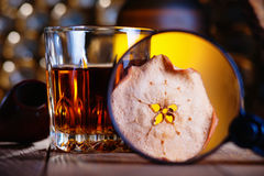 Glass of whiskey, magnifying glass, dried apple and smooking pipe. Whiskey, magnifying glass, dried apple and smooking pipe stock photo