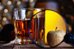 Glass of whiskey, magnifying glass, golden apple and smooking pipe. Whiskey, magnifying glass, golden apple and smooking pipe royalty free stock photography