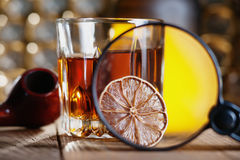 Glass of whiskey, magnifying glass, lemon and smooking pipe Royalty Free Stock Image