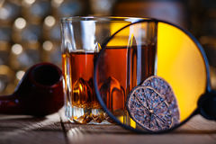 Glass of whiskey, magnifying glass, lemon and smooking pipe. On table royalty free stock photography