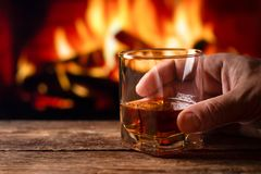 A glass of whiskey in a man hand royalty free stock image