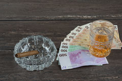Glass of whiskey and a money with cuban cigar on a grey wooden table. Top view. Royalty Free Stock Photos