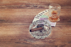 Glass of whiskey and a money with cuban cigar on a grey wooden table. Top view. Stock Image