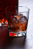 Glass of whiskey with natural ice on a wooden table Stock Photos