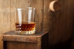 Glass of whiskey near a barrel. Tumbler glass with amber whiskey near an old wooden barrel in a cellar stock images