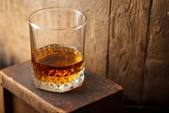 Glass of whiskey near a barrel. Tumbler glass with amber whiskey near an old wooden barrel in a cellar stock photography