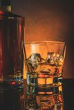 Glass of whiskey near bottle on black table with reflection, warm atmosphere Royalty Free Stock Photos