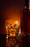 Glass of whiskey near bottle on black table with reflection, warm tint atmosphere Stock Image