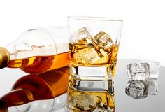 Glass of whiskey near bottle and ice cubes on black table with reflection Stock Photography