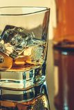 Glass of whiskey near bottle on table with reflection, warm atmosphere Royalty Free Stock Image