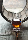 Glass of whiskey and a old barrel. Glass of a whiskey on the background of old barrel Stock Images