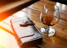 Glass of whiskey or other strong amber alcoholic beverage and leather brown purse on black reflecting table top studio background stock photos