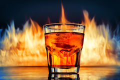 Glass of Whiskey over burning flames background Stock Photos