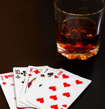 Glass of whiskey and playing cards on a black desk on the wooden table. Angle view, identification cards Stock Photography