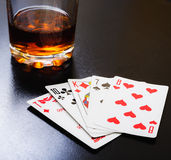 Glass of whiskey and playing cards on a black desk on the wooden table. Angle view, identification cards Royalty Free Stock Photos