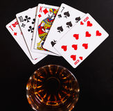 Glass of whiskey and playing cards on a black desk on the wooden table. Angle view, identification cards Royalty Free Stock Photography