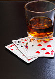 Glass of whiskey and playing cards on a black desk on the wooden table. Angle view, identification cards Royalty Free Stock Photo