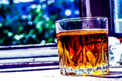 A glass of whiskey. A pleasant mix of colors of a glass of whiskey Stock Image