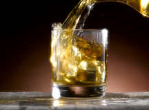 Glass of whiskey. Whiskey poured into the glass Stock Images