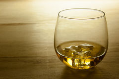Glass of whiskey shot on a wooden surface. A glass of whiskey shot on a wooden table Stock Photos