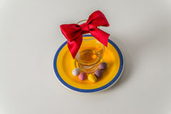 Glass of whiskey single malt, colorful sweet eggs on yellow-blue. Plate, red bow, white background Royalty Free Stock Photography