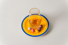 Glass of whiskey single malt, colorful sweet eggs on yellow-blue. Plate, white background Stock Photos