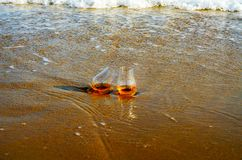 Glass of whiskey single malt on the sand washed by the waves, a. Glass of tasting, relax on the beach, vacation royalty free stock image