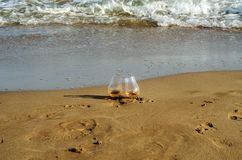 Glass of whiskey single malt on the sand washed by the waves, a. Glass of tasting, relax on the beach, vacation royalty free stock photos