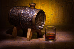 Glass of whiskey and small barrel on wooden table. Glass of whiskey and small vantage barrel on old wooden table with yellow background. Vintage stilllife royalty free stock photo