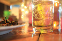 A glass of whiskey and some food. A glass of whiskey and some food on the table at the bar Stock Photos