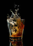 Glass of whiskey with splash, isolated on black Royalty Free Stock Image