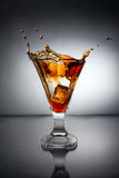Glass with whiskey splash Stock Photos