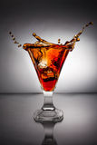 Glass with whiskey splash Royalty Free Stock Photography