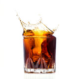 Glass with whiskey splash Royalty Free Stock Images