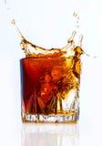 Glass with whiskey splash on white Royalty Free Stock Photos