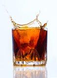 Glass with whiskey splash on white Royalty Free Stock Image