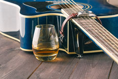 Glass of whiskey on the table and guitar Royalty Free Stock Images
