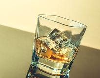 Glass of whiskey on table with reflection, warm atmosphere Stock Images