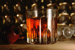 Glass of whiskey and tobacco pipe Stock Photos
