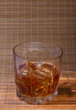 Glass of whiskey. Glass tumbler of whiskey with ice cubes Royalty Free Stock Photos