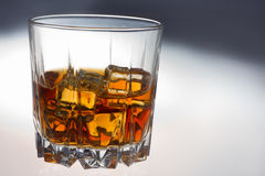 Glass of whiskey. Glass tumbler of whiskey with ice cubes Royalty Free Stock Images