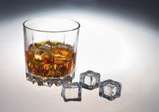 Glass of whiskey. Glass tumbler of whiskey with ice cubes Royalty Free Stock Photo
